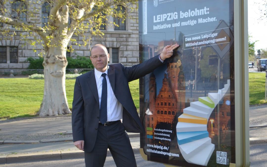 """Wirtschaftsbürgermeister Uwe Albrecht präsentiert das Plakat der Kampagne """"Mittelstandsförderprogramm"""" der Wirtschaftsförderung Leipzig; Foto: Andreas Reichelt"""